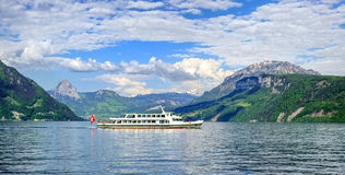 Cruise ship on Lake Lucerne, Alps mountains, Switzerland. Cruise ship in front of green alpine meadows and snow covered peaks of Alps mountains on Lake Lucerne Royalty Free Stock Images