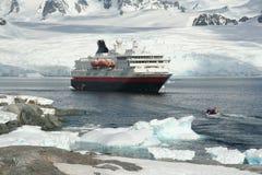 Cruise ship, landing party. In glacier filled bay, Petermann Island,Antarctica stock photos