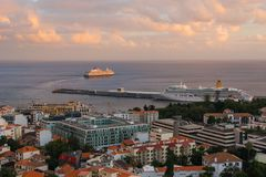 A cruise ship leaves a port at sunset. Two ships at sunset. One leaves to the sea, the other is still in the harbor. Cloudy skies are pale pink and peach stock photo