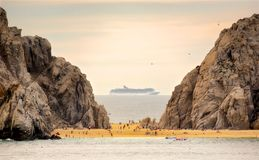 Cruise Ship between cliffs. Leaving Cabo San Lucas. Cruise ship sails by in the distance as sun seekers enjoy the early evening heat on Land`s End. Cabo San Stock Photos