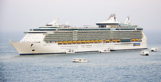 Cruise ship Liberty of the Seas and Tender Boats. The Royal Caribbean Liberty of the Seas anchored of the coast of Belize City as tenders prepare to pick up Royalty Free Stock Photo