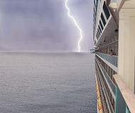 Cruise ship and lightning. A big cruise ship sailing across the ocean, stormy sky with a lightning in the background Stock Images