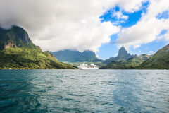 Moorea, cruise ship in Pacific Ocean. Cruise ship at Moorea - green and turquoise water in the reef and mountains in Clouds with dark green forests royalty free stock photography