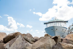 Cruise Ship Moored Beyond Boulders. Luxury Cruise Ship Beyond Boulders with Ropes to Pier Royalty Free Stock Image