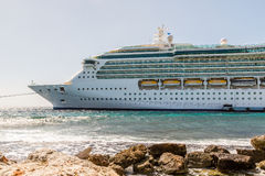 Cruise Ship Moored in Sun by Seawall Royalty Free Stock Image