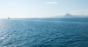 Cruise ship near the horizon with a mountain in the background. Cruise ship on the mediterranean sea near Italy, calm sea Royalty Free Stock Photos