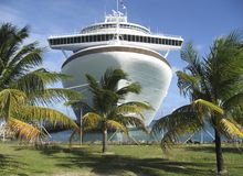 Cruise Ship and Palm Trees. A massive cruise ship is shown framed by palm trees Stock Images