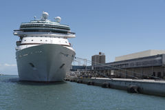 Cruise ship and passenger terminal. Cruise ship alongside with ropes attached to a passenger terminal Stock Images