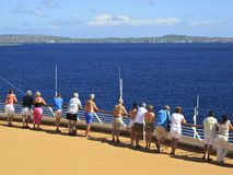 Cruise ship passengers on the deck arriving in Caribbean port Stock Photos