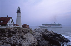 Cruise Ship Passing Portland Head Lighthouse. Landmark lighthouse at Portland Head overlooking Atlantic Ocean as cruise ship sails by Stock Image
