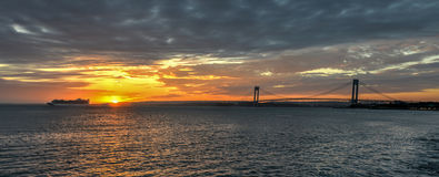 Cruise ship passing Verrazano Narrows Bridge At Sunset. A cruise ship passing the Verrazano Narrows Bridge at sunset from Brooklyn. The bridge a double-decked stock photo