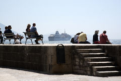 Cruise ship and people on a seawall. DUBROVNIK HARBOR CROATIA - MAY 2016 - Tourists to Debrovnik harbor sitting on the harbor wall relaxing in the sunshine royalty free stock images