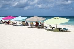Oranjestad, Aruba - April 10, 2018: Cruise ship people sunbathing under colorful umbrellas on Eagle Beach. Cruise ship people sunbathing under colorful umbrellas stock photography