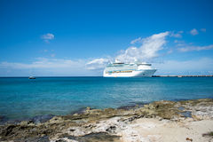 Cruise ship at pier in Caribbean Islands. Large cruise ship at pier in Caribbean Islands near rocky shoreline with small boat in distant view Stock Photos