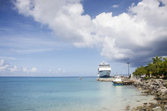 Cruise Ship at Pier near Tugboat. A cruise ship docked at a pier with a nearby Tugboat Stock Photo