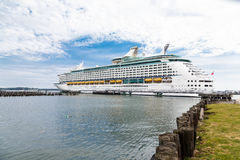 Cruise Ship Between Point of Land and Wood Pilings Stock Photo