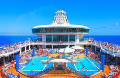 Cruise ship pool deck. People and children enjoying a cruise ship pool deck under a blue sky