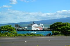 Cruise ship at port of call. Cruise ship is docked at island harbor with blue water, blue mountains and blue sky Stock Photos