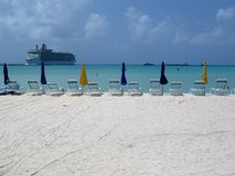 Cruise ship at port in St Marten. Chairs and umbrellas on the beach in St Marten, Virgin Islands with cruise ship Royalty Free Stock Images