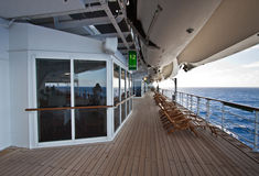 Cruise ship promenade view. Down the length of a long teak deck for taking daily exercise overlooking the ocean royalty free stock images