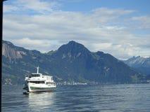 The cruise ship promotes passengers around Lake Lucerne. A cruise ship on Lake Lucerne in front of a mountainous bottom Stock Photo
