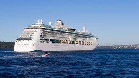 Cruise ship Radiance of the seas, Sydney. Sydney - February 25, 2016: a huge sea liner Radiance of the seas came from Sydney harbor cruise and a small sailing Royalty Free Stock Photo