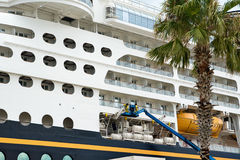 Cruise Ship Repairs. Workers on a lift inspecting and making repairs to a cruise ship in port royalty free stock images