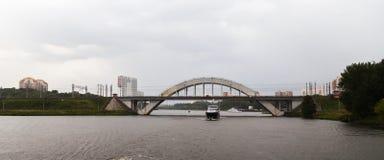 Cruise ship on the river under the bridge. Cruise ship sets sail on the river under the arc-shaped bridge Royalty Free Stock Image