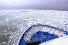 Cruise ship's bow over frozen field of ice floats. Stock Photo