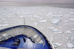 Cruise ship's bow over frozen field of ice floats. Stock Images