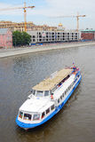 Cruise ship sail on the Moscow river. Chirst the Savior church cupola is seen at background. Along the river, on Preshictenskaya embankment many people ride Stock Image