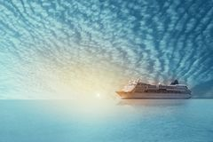 Cruise ship sailing in the sea on sunset and twilight with fluffy clouds. Cruise ship sailing in the sea on sunset and twilight with fluffy white tiny clouds royalty free stock photo