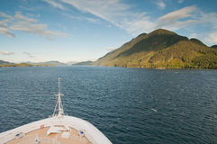 Cruise ship sailing towards mountain Stock Image