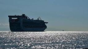 A cruise ship sails into the sunset as it leaves the Port of Vancouver.  stock footage