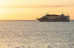 Cruise ship sails to setting sun Stock Photography