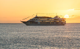 Cruise ship sails to setting sun Stock Photography