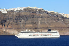 Cruise ship in santorini. Big luxury cruise liner docked next to the volcanic shores of santorini island Stock Photo