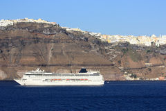 Cruise ship in santorini. Big luxury cruise liner docked next to the volcanic shores of santorini island Royalty Free Stock Photos