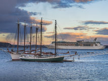 Cruise ship and schooners at sunset Royalty Free Stock Images