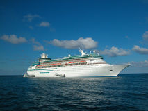 Cruise Ship At Sea. A large cruise ship with calm waters beneath and a blue sky above Royalty Free Stock Photo