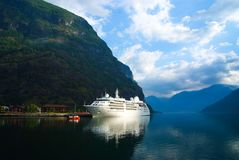 Cruise ship in sea port on mountain landscape in Flam, Norway. Ocean liner in sea harbor with green mountains. Cruise. Destination and travel. Summer vacation Royalty Free Stock Photo