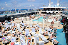 Cruise Ship At Sea. As passengers enjoy the pool and relaxing in the sun Stock Photo