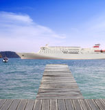 Cruise ship on the sea and wood dock Stock Image