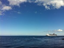 Cruise Ship seen from Catalina Island, California. See the cruise ship in the water in the distance, and the clouds overhead in the blue sky Royalty Free Stock Photography