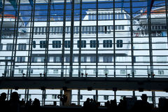 Cruise ship seen from inside terminal. At the start of a vacation, silhouettes of people are seen milling around inside the terminal at a cruise ship pier.  The Royalty Free Stock Image