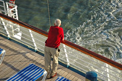 Cruise Ship Senior. A senior looks over the rail at the rear of a cruise ship royalty free stock images