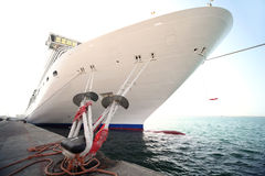 Cruise ship standing in dock. Big white cruise ship standing in dock, mooring with ropes Stock Photo