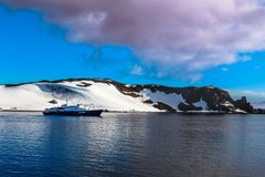 Cruise ship standing still on the sea surface with snow covered. Mountains in the background, close to Half Moon island, Antarctic