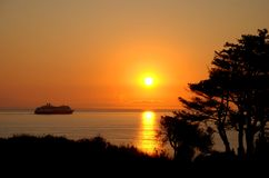 Cruise Ship and Sunset. A cruise ship sails on a calm ocean into a orange sunset royalty free stock photos