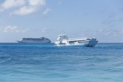 Cruise Ship and Tender. A tender boat leaving from an anchored cruise ship in tropical waters Stock Photography